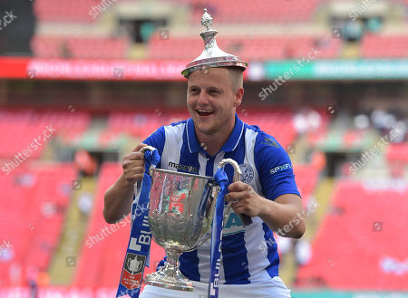 Shane Cooper-Clark of Thatcham Town celebrates with The VA Vase trophy