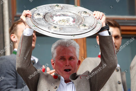 Bayern coach Jupp Heynckes lifts the trophy on the balcony of the town hall at Marienplatz square celebrating the 28th Bundesliga title at the German first division Bundesliga in Munich, Germany