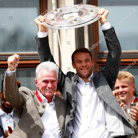 Bayern coach Jupp Heynckes, left, and goalie Manuel Neuer celebrate with the team on the balcony of the town hall at Marienplatz square the 28th Bundesliga title at the German first division Bundesliga in Munich, Germany