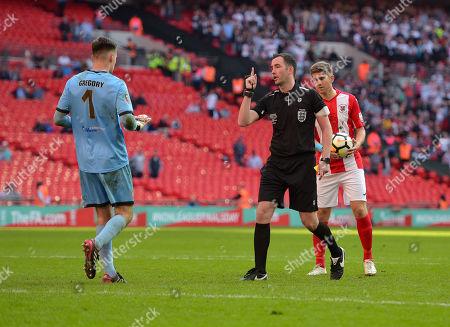 Referee Chris Kavanagh warns Bromley Goalkeeper David Gregory before Matt Lowe of Brackley Town takes his penalty