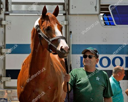 Assistant trainer Jimmy Barnes holds Preakness Stakes and Kentucky Derby winner Justify as a crowd welcomes the horse back to Barn 33 at Churchill Downs in Louisville, Ky., . Justify will attempt to become the winner of horse racing's Triple Crown in June in New York at The Belmont Stakes