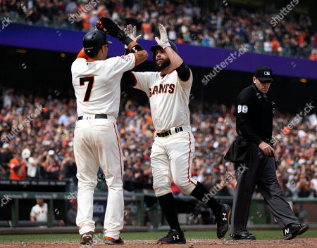 San Francisco Giants right fielder Gorkys Hernandez, left, congratulates Brandon Belt, right, on his three-run home run against the Colorado Rockies during the seventh inning of a Major League Baseball game, in San Francisco. Evan Longoria also scored. Umpire is Chris Conroy