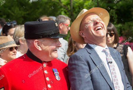 Designer Joe Swift laughs at a joke by a Chelsea Pensioner
