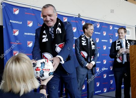 Ian Ayre, left, hands over a soccer ball after posing for pictures at a news conference where he was introduced as the first chief executive officer of the Nashville MLS franchise, in Nashville, Tenn. Ayre is a former CEO of Liverpool Football Club of the English Premier League