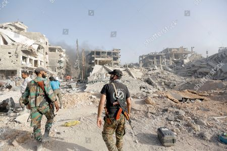 Syiran solders walk through destroyed parts of al-Hajar al-Aswad neighborhood in south Damascus, Syria, 21 May 2018. According to reports, the Syrian army claims it has regained full control over Damascus' surrounding areas. State TV reports that the army cleared the area and the adjacent al-Yarmouk camp after killing large number of ISIS fighters.