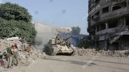 Soldiers ride atop a tank in destoyed parts of the Yarmouk camp neighborhood in south Damascus, Syria, 21 May 2018. According to reports, the Syrian army claims it has regained full control over Damascus' surrounding areas. State TV reports that the army cleared the area and the adjacent al-Yarmouk camp after killing large number of ISIS fighters.
