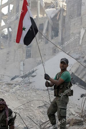 A Syrian soldier holds up the national flag at al-Hajar al-Aswad neighborhood in south Damascus, Syria, 21 May 2018. According to reports, the Syrian army claims it has regained full control over Damascus' surrounding areas. State TV reports that the army cleared the area and the adjacent al-Yarmouk camp after killing large number of ISIS fighters.