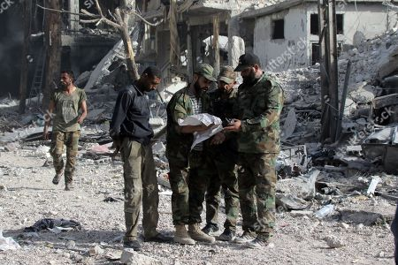 Syrian soldiers look at a map in al-Hajar al-Aswad neighborhood in south Damascus, Syria, 21 May 2018. According to reports, the Syrian army claims it has regained full control over Damascus' surrounding areas. State TV reports that the army cleared the area and the adjacent al-Yarmouk camp after killing large number of ISIS fighters.