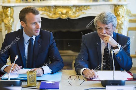 French President Emmanuel Macron speaks, flanked by former Environment Minister Jean-Louis Borloo, in charge of a mission on the priority neighbourhoods in the French urban policy, during the presentation of a battle plan for the country's most deprived areas, in Paris
