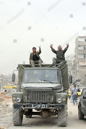 Syrian soldiers flash the victory sign after recapturing the Yarmouk Camp district in south Damascus, Syria, 22 May 2018. Media reports state the Syrian government of Bashar al-Assad on 21 May recaptured the last area of Damascus under opposition control and took full control of the capital for the first time since the outbreak of the civil war in 2011, after groups of Islamic State (IS) fighters holed up in an area of south Damascus, including the Palestinian refugee camp Yarmouk, were bussed out.