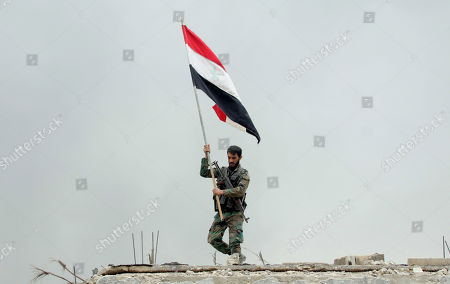 A Syrian soldier places the national flag atop a government institution in the Yarmouk Camp district in south Damascus, Syria, 22 May 2018. Media reports state the Syrian government of Bashar al-Assad on 21 May recaptured the last area of Damascus under opposition control and took full control of the capital for the first time since the outbreak of the civil war in 2011, after groups of Islamic State (IS) fighters holed up in an area of south Damascus, including the Palestinian refugee camp Yarmouk, were bussed out.stockképe
