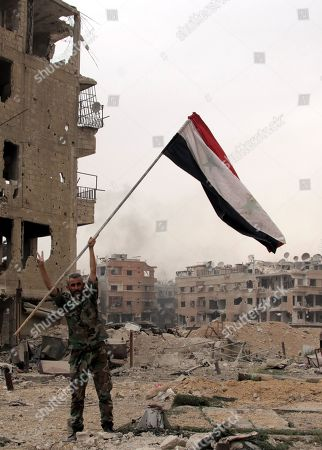 A Syrian soldier holds up the national flag at the Yarmouk Camp district in south Damascus, Syria, 22 May 2018. Media reports state the Syrian government of Bashar al-Assad on 21 May recaptured the last area of Damascus under opposition control and took full control of the capital for the first time since the outbreak of the civil war in 2011, after groups of Islamic State (IS) fighters holed up in an area of south Damascus, including the Palestinian refugee camp Yarmouk, were bussed out.stockképe