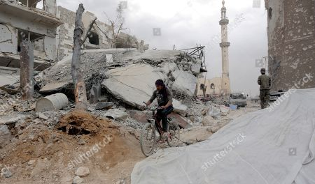 A man rides a bicycle amid damaged building at the Yarmouk Camp district in south Damascus, Syria, 22 May 2018. Media reports state the Syrian government of Bashar al-Assad on 21 May recaptured the last area of Damascus under opposition control and took full control of the capital for the first time since the outbreak of the civil war in 2011, after groups of Islamic State (IS) fighters holed up in an area of south Damascus, including the Palestinian refugee camp Yarmouk, were bussed out.stockfényképe