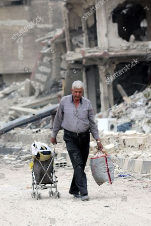 A man carries belongings and walk at the Yarmouk Camp district in south Damascus, Syria, 22 May 2018. Media reports state the Syrian government of Bashar al-Assad on 21 May recaptured the last area of Damascus under opposition control and took full control of the capital for the first time since the outbreak of the civil war in 2011, after groups of Islamic State (IS) fighters holed up in an area of south Damascus, including the Palestinian refugee camp Yarmouk, were bussed out.
