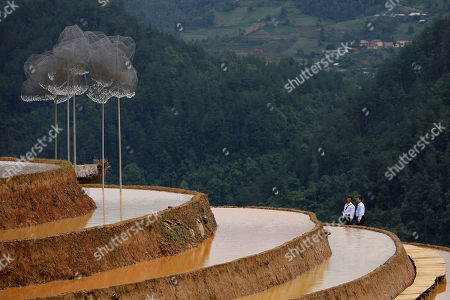 Visitors look at an art installation 'Crystal Cloud' on a terraced rice field in La Pan Tan commune, Mu Cang Chai, Yen Bai province, 22 May 2018. The project by two landscape designers Andy Cao and Xavier Perrot, featured around 58,000 crystal beads, has bought different opinions from the public as people concern it may harm the natural scenery. The 'Crystal Cloud' exhibition was expected to open for tourists for five months at first, has now shortened to two weeks, starting from 19 May 2018, according to local media. It costs each visitor 30,000 VND (around 1,5 US dollars) to by a ticket for the exhibition.