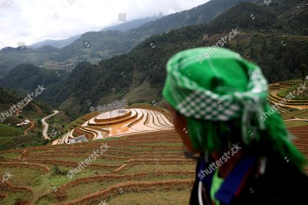 A Vietnamese ethnic woman looks at an art installation 'Crystal Cloud' on a terraced rice field in La Pan Tan commune, Mu Cang Chai, Yen Bai province, 22 May 2018. The project by two landscape designers Andy Cao and Xavier Perrot, featured around 58,000 crystal beads, has bought different opinions from the public as people concern it may harm the natural scenery. The 'Crystal Cloud' exhibition was expected to open for tourists for five months at first, has now shortened to two weeks, starting from 19 May 2018, according to local media. It costs each visitor 30,000 VND (around 1,5 US dollars) to by a ticket for the exhibition.
