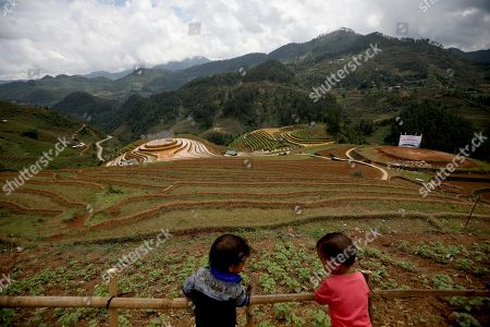 Vietnamese ethnic boys play near an art installation 'Crystal Cloud' on a terraced rice field in La Pan Tan commune, Mu Cang Chai, Yen Bai province, 22 May 2018. The project by two landscape designers Andy Cao and Xavier Perrot, featured around 58,000 crystal beads, has bought different opinions from the public as people concern it may harm the natural scenery. The 'Crystal Cloud' exhibition was expected to open for tourists for five months at first, has now shortened to two weeks, starting from 19 May 2018, according to local media. It costs each visitor 30,000 VND (around 1,5 US dollars) to by a ticket for the exhibition.
