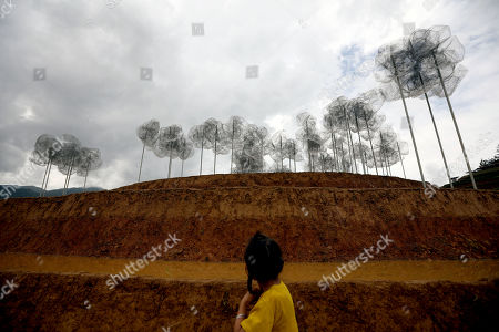 A Vietnamese ethnic girl walks near an art installation 'Crystal Cloud' on a terraced rice field in La Pan Tan commune, Mu Cang Chai, Yen Bai province, 22 May 2018. The project by two landscape designers Andy Cao and Xavier Perrot, featured around 58,000 crystal beads, has bought different opinions from the public as people concern it may harm the natural scenery. The 'Crystal Cloud' exhibition was expected to open for tourists for five months at first, has now shortened to two weeks, starting from 19 May 2018, according to local media. It costs each visitor 30,000 VND (around 1,5 US dollars) to by a ticket for the exhibition.