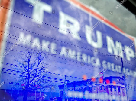 The Campbell County Court is reflected in a window decorated with a Donald Trump campaign sign in Jacksboro, Tenn