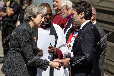 Prime Minister Theresa May is greeted by dignitaries, including Bishop David Walker Archbishop of York John Sentamu, SIR Richard Leese and Andy Burnham (shaking hands), at Manchester Cathedral ahead of a Service of Remembrance on the first anniversary of the Manchester Arena bombing.