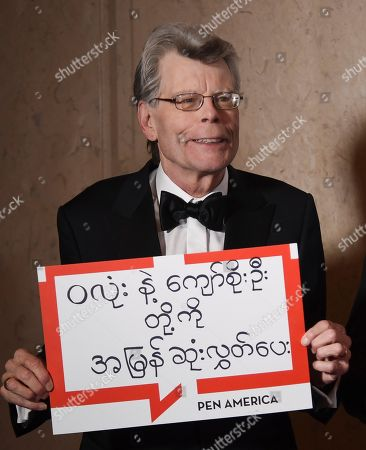PEN America literary service award recipient Stephen King holds a sign in support of detained Myanmar journalists Wa Lone and Kyaw Soe Oo at the 2018 PEN Literary Gala at the American Museum of Natural History, in New York