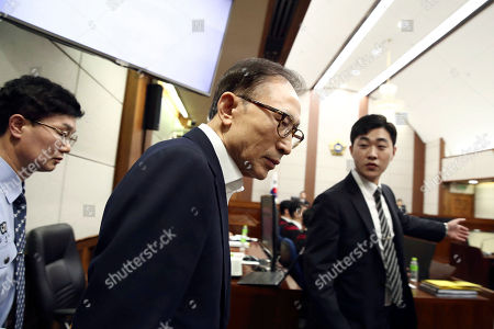 Former South Korean President Lee Myung-bak, center, appears for his first trial at the Seoul Central District Court in Seoul . A South Korea court issued an arrest warrant for Lee on corruption charges on March 23, 2018