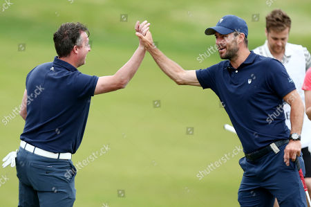 Ex Liverpool footballers Robbie Fowler and Jamie Redknapp high five on the 18th hole.