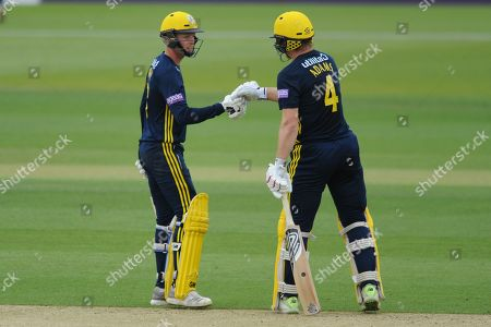 Brad Taylor(left) and Jimmy Adams of Hampshire punch gloves as Jimmy Adams finds the boundary  during the Royal London One Day Cup match between Hampshire County Cricket Club and Essex County Cricket Club at the Ageas Bowl, Southampton. Picture by Dave Vokes