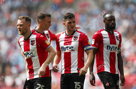 Jordan Moore-Taylor of Exeter City is pulled away by Jordan Tillson of Exeter City after arguing with team mate Christy Pym of Exeter City