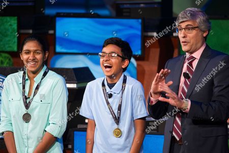 30th National Geographic Bee Championship winner Venkat Ranjan, of San Ramon, Calif., center, 2nd place finisher Anoushka Buddhikot, of N.J., left, and host Mo Rocca stand onstage after the final round, at the National Geographic Society in Washington