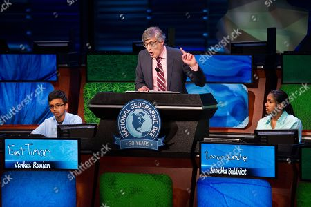 Host Mo Rocca asks a question of the two finalists, Venkat Ranja, of San Ramon, Calif, left and Anoushka Buddhikot, of N.J. during their final championship round in the 30th National Geographic Bee Championship final round at the National Geographic Society in Washington