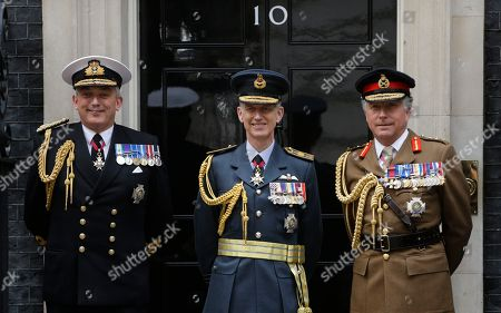 First Sea Lord and head of the British Royal Navy, Admiral Philip Jones, left, with Air Chief Marshal Stephen Hillier, centre, who is head of the British Royal Air Force and Chief of the General Staff General Nick Carter who is head of the British Army pose for a picture by a defence photographer in Downing Street in London, . The military chiefs are attending a reception at 10 Downing Street to celebrate the centenary of the RAF, which was formed in April 1918, out of elements of the army and naval flying corps