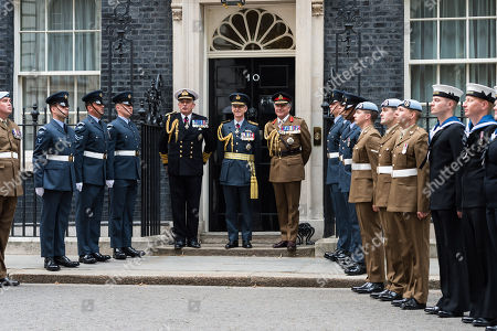 Stock Picture of Air Chief Marshal Sir Stephen Hillier (C), Admiral Sir Philip Jones (CL) and General Sir Nick Carter (CR) stand among military personnel outside 10 Downing Street.
