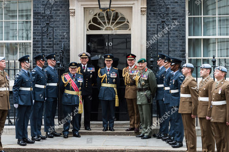 Air Chief Marshal Sir Stephen Hillier (C), Admiral Sir Philip Jones (CL) and General Sir Nick Carter (CR) stand together with veterans and junior military personnel outside 10 Downing Street.