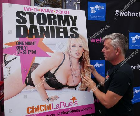 Stock Picture of A man places a poster of former adult actress Stormy Daniels, also known as Stephanie Clifford, outside the Chi Chi LaRue clothing store prior to Daniels receiving the  key to the city of West Hollywood in California, USA, 23 May 2018.