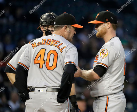 Stock Image of Chance Sisco, Roger McDowell, Alex Cobb. Baltimore Orioles pitching coach Roger McDowell (40) talks with starting pitcher Alex Cobb, right, and catcher Chance Sisco during the third inning of a baseball game against the Chicago White Sox, in Chicago