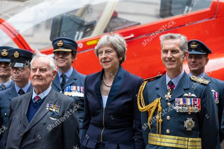 Prime Minister Theresa May, 92-year-old WW2 pilot Colin Bell (centre-left) and Air Chief Marshal Sir Stephen Hillier(centre-right) pose for a photograph with members of the RAF in front of a Red Arrow jet as part of the RAF100 Centenary celebrations.