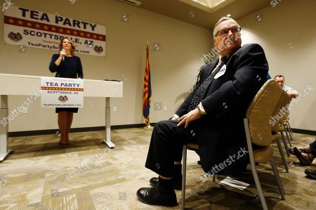 Republican Senate candidates Kelli Ward, left, and former Maricopa Country Sheriff Joe Arpaio, right, listen to a question from the audience as the candidates talk about their platform policies at a Scottsdale Tea Party event in Scottsdale, Ariz. Arizona conservatives are torn between two icons of their movement - Arpaio and former state senator Ward - in the GOP Senate primary