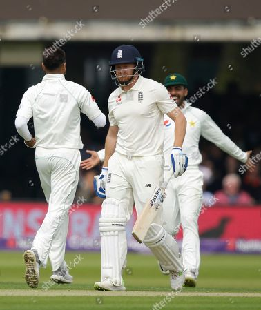 England's Jonathan Bairstow, centre walks off the pitch after he is bowled by Pakistan's Faheem Ashraf, left, during the first day of play of the first test cricket match between England and Pakistan at Lord's cricket ground in London