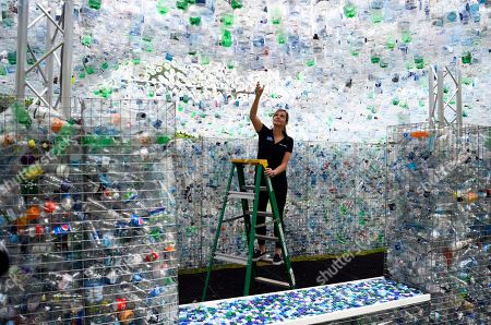 Stock Picture of A worker places a finishing touch to the sculpture 'Waste of Space' by British artist Nick Wood at London Zoo in London, Britain, 24 May 2018. Waste of Space is an installation made from 15,000 discarded single use bottles collected from London's waterways. The sculpture represents the amount of single use bottle that are purchased every minute in Britain.