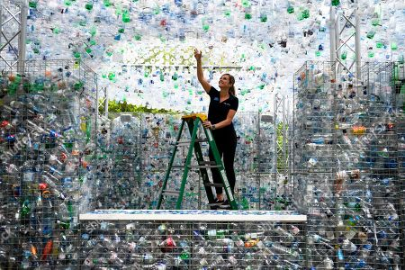 Stock Photo of A worker places a finishing touch to the sculpture 'Waste of Space' by British artist Nick Wood at London Zoo in London, Britain, 24 May 2018. Waste of Space is an installation made from 15,000 discarded single use bottles collected from London's waterways. The sculpture represents the amount of single use bottle that are purchased every minute in Britain.