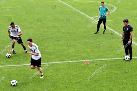 German national soccer team's head coach Joachim Loew (R) and assistant coach Miroslav Klose (2-R) look to Jonathan Tah (L) and Mesut Oezil (2-L)  during a training session in Eppan, Italy, 24 May 2018. The German squad prepares for the upcoming FIFA World Cup 2018 soccer championship in Russia at a training camp in Eppan, South Tyrol, until 07 June 2018.