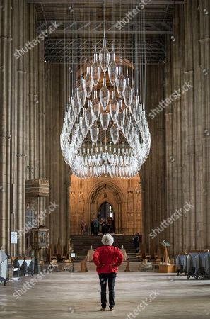 Artist Monica Guggisberg (in red) walks under a sculpture entitled 'Boat of Remembrance, 2018' - a 20-metre installation of 100 glass amphorae suspended in the shape of a ship high above the Nave of Canterbury Cathedral. A series of glass installations by artists Philip Baldwin and Monica Guggisberg reflecting on themes of war and remembrance, migration and refugees are going on display at the cathedral commemorating the 100th anniversary of the end of the First World War.