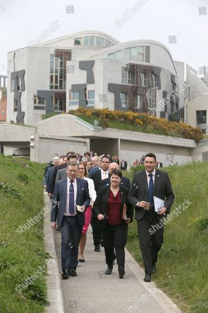 Stock Photo of Planting of Holyrood poppy tribute, - Alexander Stewart, Ruth Davidson, Leader of the Scottish Conservative and Unionist Party, and Miles Briggs at the head of a group of MSPs make their way to gardens outside The Scottish Parliament to plant poppy seeds as part of the nationwide Ribbon of Poppies campaign.