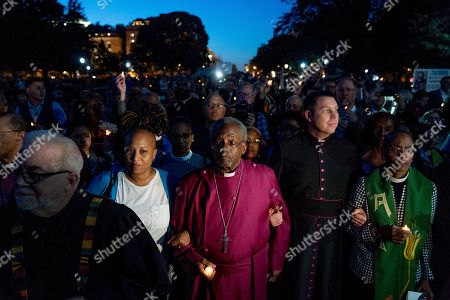 The Most Rev. Michael Curry, center, the presiding bishop of the U.S. Episcopal Church, who spoke at the royal wedding of Prince Harry and Meghan Markle, and others take part in a candlelight vigil outside the White House, in Washington. According to organizers, the event was intended to bring attention to political, moral and theological issues in America