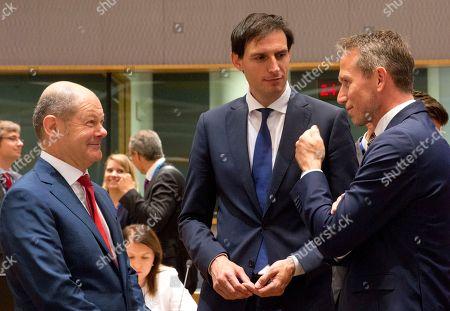 German Finance Minister Olaf Scholz, left, speaks with Danish Finance Minister Kristian Jensen, center, and Dutch Finance Minister Wopke Hoekstra, center, during a meeting of EU finance ministers at the Europa building in Brussels on