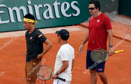 Japan's Kei Nishikori, left, trains with coaches Michael Chang, of the U.S, center, and Argentina's Dante Bottini at the Roland Garros stadium in Paris, . The French Open tennis tournament starts Sunday