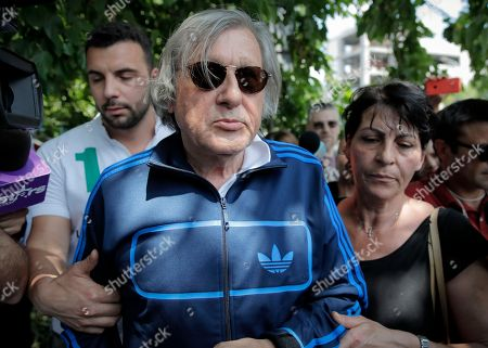 Former tennis player Ilie Nastase walks after being released from the traffic police headquarters in Bucharest, Romania, following his second arrest within hours, first on suspicion of driving while drunk and refusing to take a breathalyzer test, and then for riding a scooter without a license and breaking traffic law