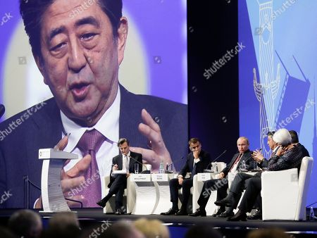 Shinzo Abe, John Micklethwait, Emmanuel Macron, Vladimir Putin, Christine Lagarde. Japanese Prime Minister Shinzo Abe, third right, also seen at a big screen, gestures as Bloomberg Editor-in-Chief John Micklethwait, left, French President Emmanuel Macron, second left, Russian President Vladimir Putin, third right, and International Monetary Fund (IMF) Managing Director Christine Lagarde, right, listen to him at the St. Petersburg International Economic Forum in St. Petersburg, Russia