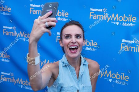Samantha Busch is seen taking a selfie at the Walmart Family Mobile tent during the Speed Street festival, in Charlotte, N.C